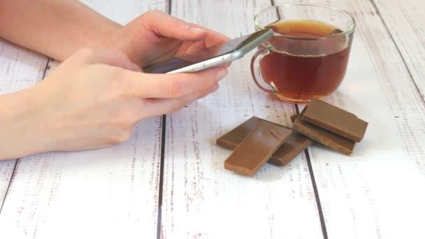 Kezében egy lány birtoklása egy smartphone egy kávézó közeli. Az asztalon van egy csésze tea, csokoládé. Technológia az életben.