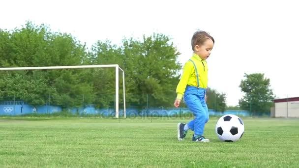 Egy gyermek, egy futballpálya játszik egy futball-labda, a lassú mozgás