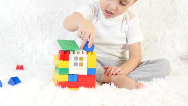 Chlapečku, staví dům hraček z barevných bloků, sedí na bílém pozadí, detail. Děti a hračky.