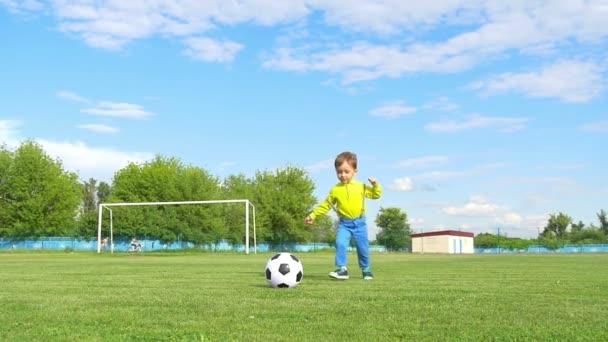 dítě začíná fotbalový míč na pozadí fotbalová branka