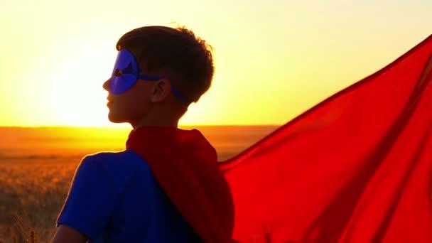 Bambino ragazzo vestito in un costume da supereroe fissando la distanza al tramonto