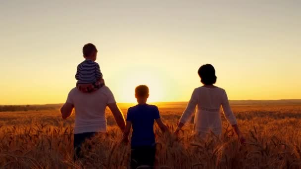 glückliche Familie spaziert bei Sonnenuntergang am Weizenfeld entlang.
