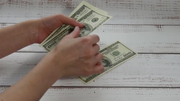 Ženské ruce spočítat 200 dolarů peněz poukázky. Peníze se vrhne na stůl