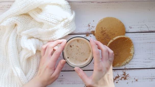 Snídaně s cappuccinem a domácí lívanečky na dřevěný stůl. Holky rukou otočením hrnek kávy. Zpomalený pohyb