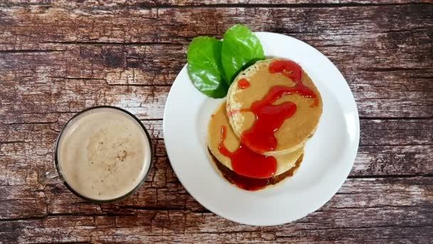Snídaně s cappuccinem a domácí lívanečky na dřevěný stůl. Pomalý pohyb