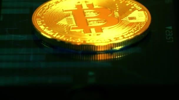 Arany érme bitcoin, feküdt a képernyőn egy kép a grafikon, idézetek, titkosító valuta. Blockchain technológia.