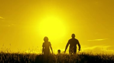 Happy family walking, holding hands at sunset.