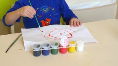 The child paints with watercolors on a white sheet of paper sitting at the table. Close-up.