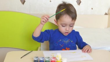 The child paints with watercolors on a white sheet of paper sitting at the table.