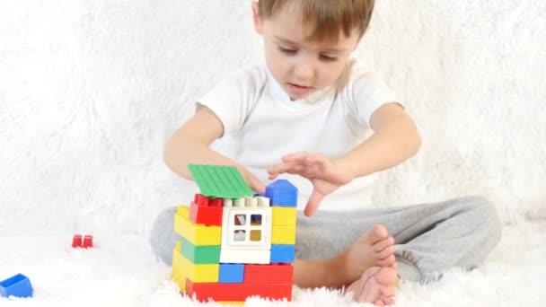 Děti staví dům hraček z barevných bloků, sedí na bílém pozadí, detail. Děti a hračky.