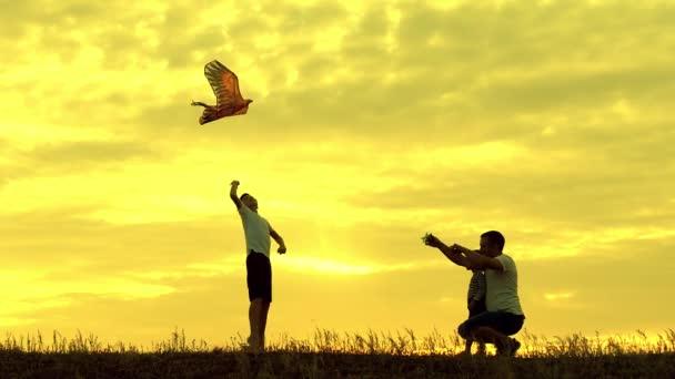 Šťastný otec rodiny a děti pobíhají v louce s drakem v létě při západu slunce v pomalém pohybu. Rodina venku, obloha je žlutá.
