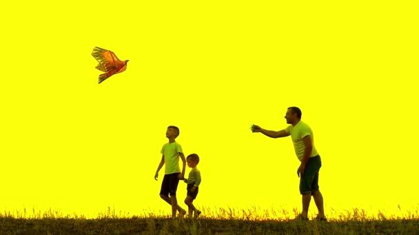 Šťastný otec se dvěma dětmi vede do oblohy draka v létě při západu slunce v pomalém pohybu. Rodina venku, obloha je žlutá. Žluté pozadí