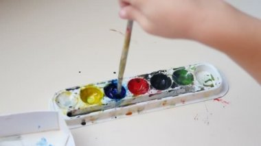 Hands child painting with watercolors on paper. The child is wetting the brush in watercolor paint.