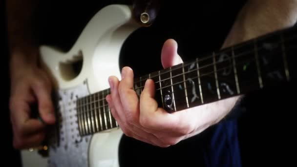 A musician plays solo on a white electric guitar on a black background. The man is playing rock.