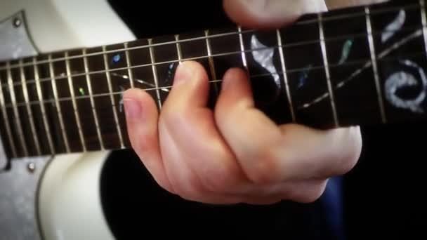 Hudebník hraje na bílém elektrickou kytaru na černém pozadí, detail. Muž se hraje rock.