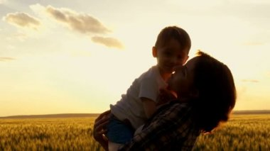 Happy Mom holds the child in his arms at sunset against the background of the wheat field. Happy family at sunset. Mother and child embrace and laugh at the sunset in a slow motion