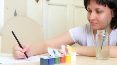 Mom draws watercolor on a white sheet of paper for his child sitting at the table. The girl draws a drawing.