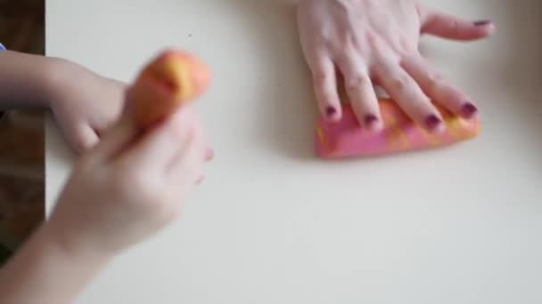 Dětské tvořivosti. Dětské ruce tvoří postavy z těsta na stole. Roztomilé dětské Plastelíny figurky na stůl