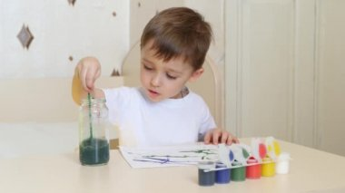 The child draws watercolor drawings on a white sheet of paper, sitting at the table.
