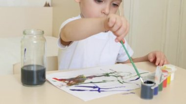 A little boy draws watercolor drawings on a white sheet of paper sitting at a table.