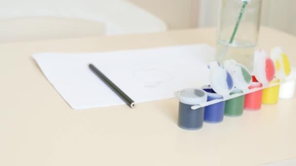 Pintura gouache, una hoja de papel, cepillos preparados para dibujar ...