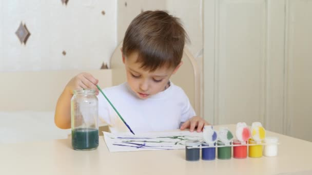 Child boy draws watercolor drawings on a white sheet of paper sitting at the table.