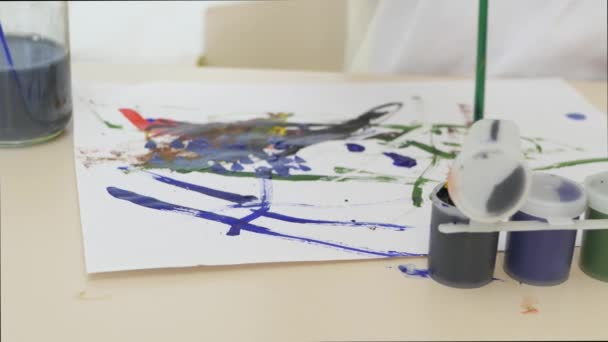 A little boy draws watercolor drawings on a white sheet of paper sitting at a table. Close-up. Motion camera slider.