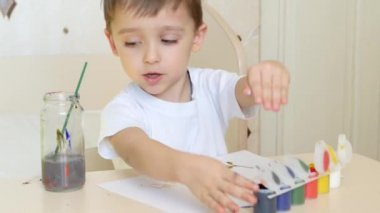 A little boy draws drawings on a white sheet of paper, with gouache paints. Close-up.