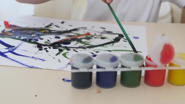 A little boy draws watercolor drawings on a white sheet of paper sitting at a table. Close-up.