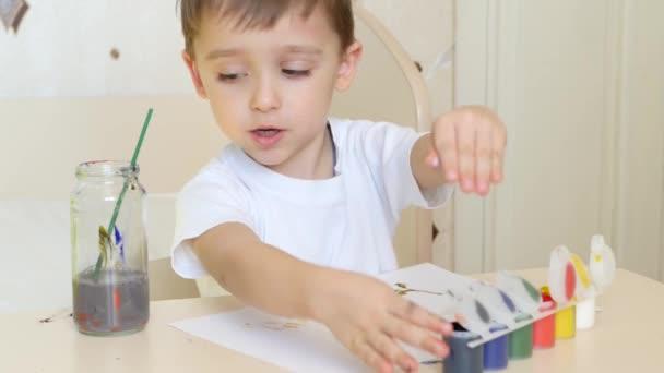 Egy kisfiú felhívja a rajzok egy fehér papírlapot, és festékek gouache. Közeli kép:.