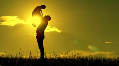 Silhouette of man and child on sunset background. The father holds the son of his sons son and kisses him at a slow pace