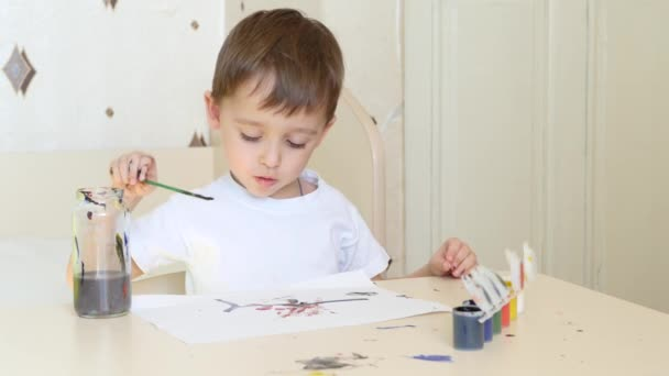 A little boy is sitting at the table and drawing with a brush on a piece of paper. Watercolor paints.