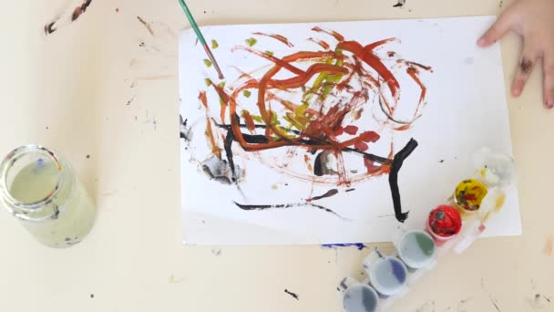 The child draws a bright sheet of paint on a white sheet of paper. Child development.