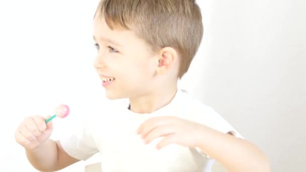 Šťastně se usmívá a olizuje lízátka na špejli, sedící u stolu na bílém pozadí