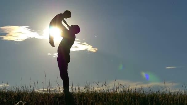 Silhouette von Vater und Sohn im Hintergrund des Sonnenuntergangs. hält der Vater die Hände seines Sohnes und küsst ihn im langsamen Tempo. das Konzept einer glücklichen Familie