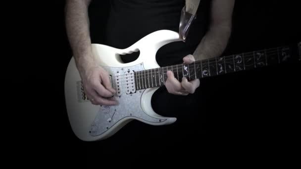 Člověk hraje sólo na bílém elektrickou kytaru na černém pozadí. Profesionální kytaru.