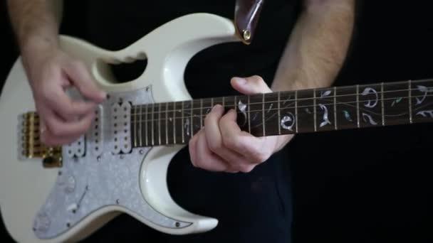 Egy ember játszik egy ritmus egy fehér és egy fekete háttér elektromos gitár. Rocksztár.
