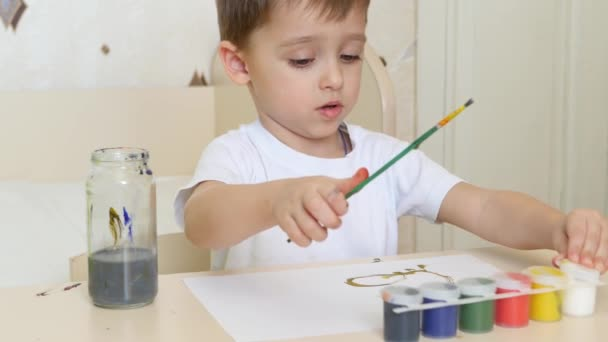 Child boy draws drawings on a white sheet of paper with gouache. Close-up.