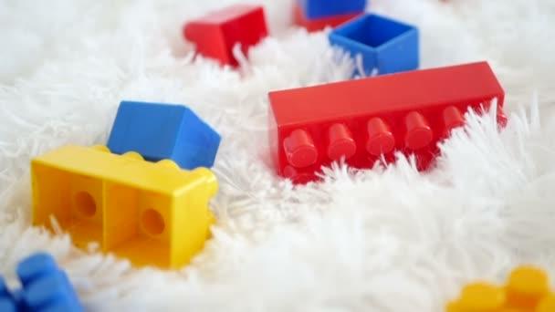 Plastové bloky barevné dětské hračky ležící na bílém pozadí