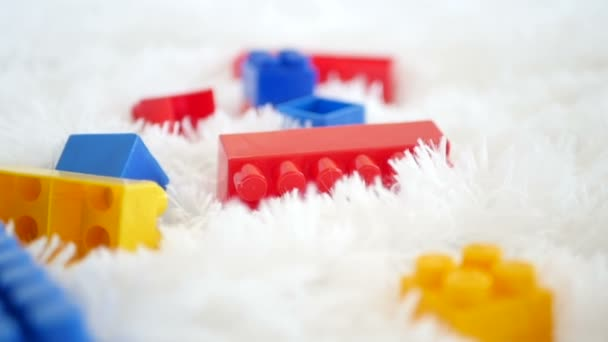 Barevné plastové bloky dětské hračky ležící na bílém pozadí. Detail