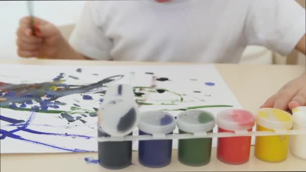 Kid draws watercolor drawings on a white sheet of paper sitting at the table. Close-up. The motion camera slider.
