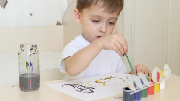 A happy child draws drawings on a white sheet of paper, with gouache sitting at the table.