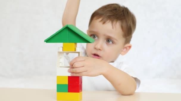 Dítě se hraje v barevné bloky, sedící u stolu na bílém pozadí. Děti a hračky. Důraz je kladen na hračky.