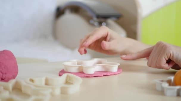 Dětské tvořivosti. Do rukou dívky tvoří růžové figurka těsta na stůl