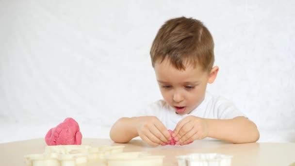 Dětské tvořivosti. Dítě s udovlstviem tvoří údaje z testu barev na stole. Roztomilé dětské Plastelíny čísla na stůl