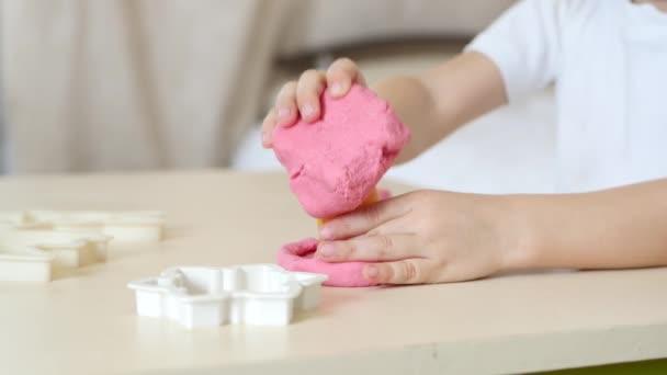 Dětské tvořivosti. Detail dětské ruce tvoří údaje z testu barev na stole. Roztomilé dětské Plastelíny figurky na stůl