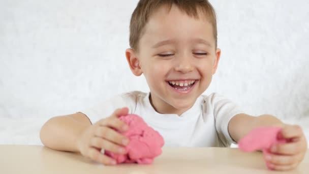 Dětské tvořivosti. Kluk s udovlstviem tvoří údaje z testu barev na stole. Roztomilé dětské Plastelíny čísla na stůl