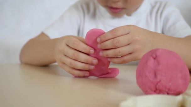 Dětské tvořivosti. Dítě tvoří údaje z testu barev na stole, detail. Pohyb kamery