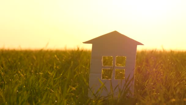 Papírna stojí na zelené trávě proti západu slunce. Paprsky procházejí oknem v papírně. Koncept šťastné rodiny, výstavby a realitních transakcí.