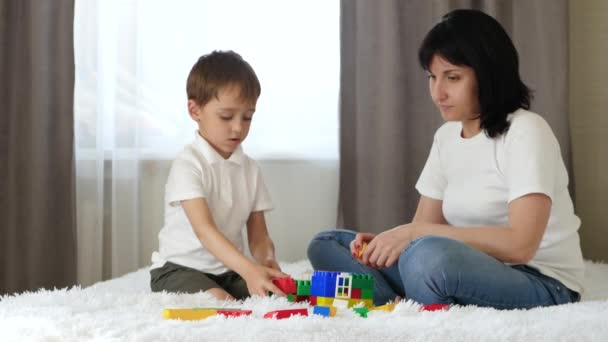 Happy family: mother and son play in building a house of colored blocks. Education and family holidays.